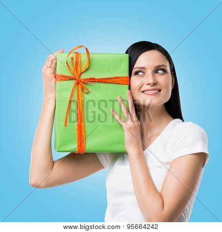 A Brunette Woman Is Holding A Green Gift Box. Blue Background.