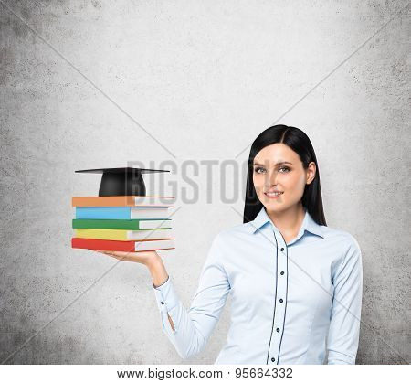 A Portrait Of A Brunette Lady With The Open Palm Who Is Holding Colourful Books And A Graduation Hat