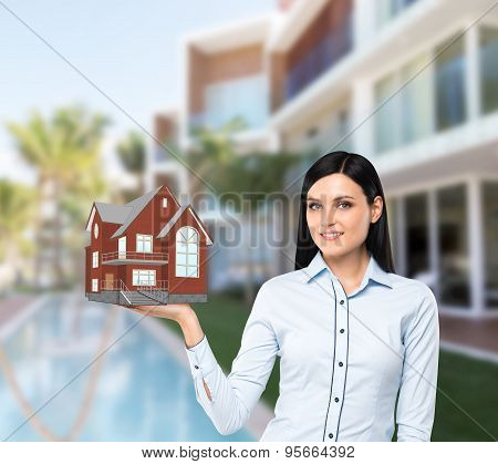 Beautiful Brunette Property Agent Presents A New House For Sale. Luxury Villa In Blur As A Backgroun