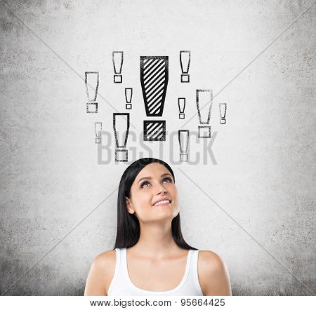 Dreamy Brunette Lady Is Looking Up. Exclamation Mark Are Drawn Above The Head. Concrete Background.