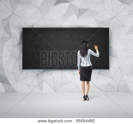 Rear View Of Full-length Brunette Woman Who Is Writing Something On The Empty Black Board.