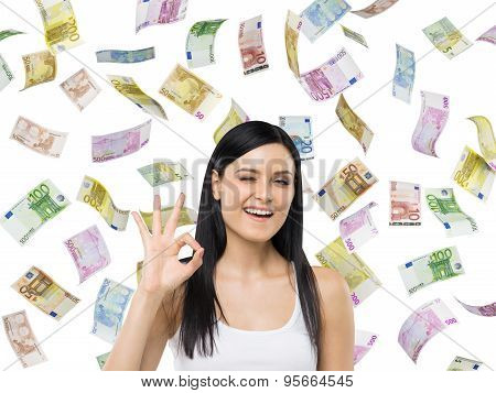 Brunette Woman Shows Ok Sign. Euro Notes Are Falling Down Over Isolated Background.