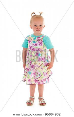 Portrait toddler girl standing in studio in summer dress isolated over white background