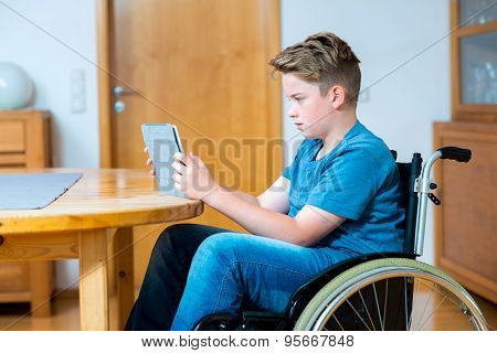Boy In Wheelchair Using Tablet Pc