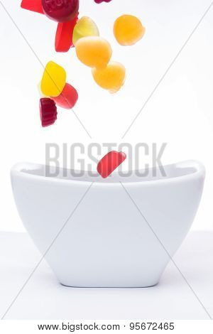 Jelly gum drops falling into a white bowl