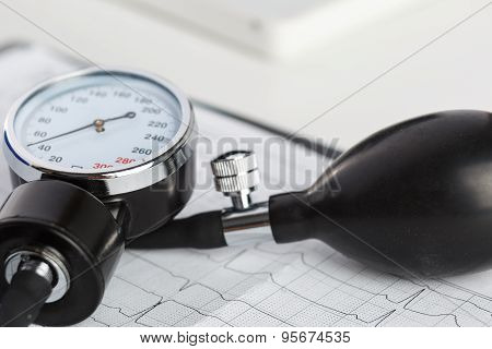 Medical Manometer Lying On Cardiogram Chart Closeup