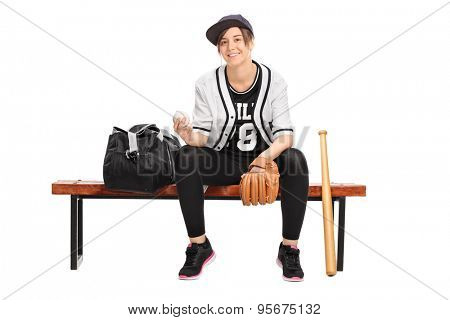 Young female athlete holding a baseball seated on a wooden bench and looking at the camera isolated on white background