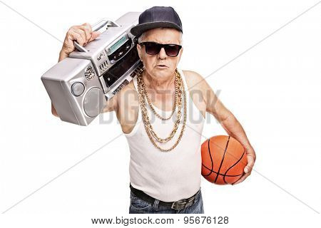 Senior man in hip hop outfit holding a ghetto blaster and a basketball isolated on white background