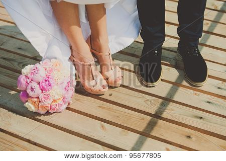 Bride and groom's shoes on the brown wooden floor with bouquet of peonies
