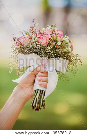 Bride holding wedding bouquet with bow