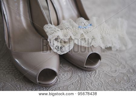 Close up of bridal wedding shoes with garter on textile background