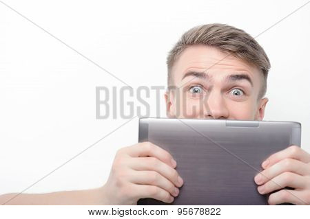 Man covering his face with tablet