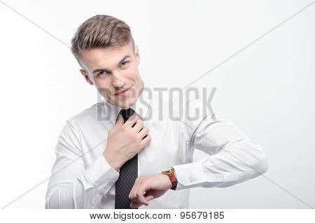 Handsome businessman fixing tie and checking time