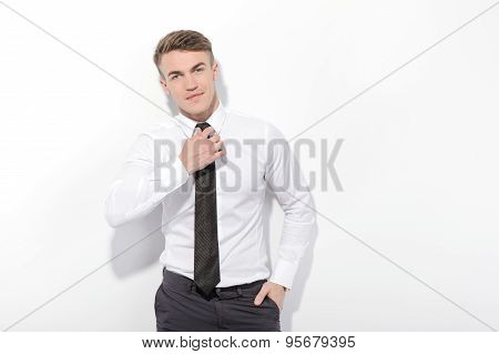 Businessman fixing his tie on isolated background
