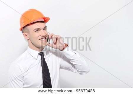 Smiling foreman talking per mobile phone