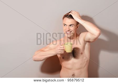 Handsome topless man holding cup of coffee
