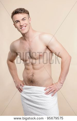 Topless man standing with towel on hips