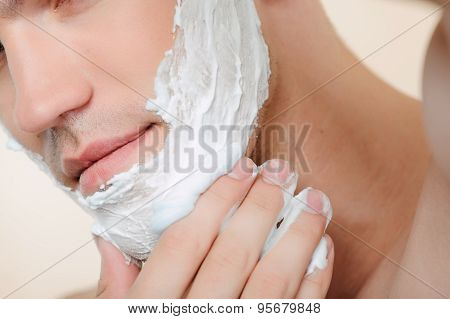 Close-up of man applying shaving mean