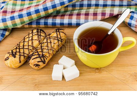 Eclairs, Black Tea In Cup And Sugar On Table