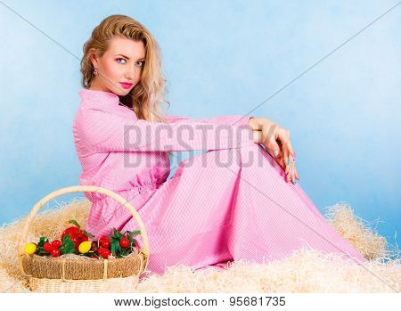 Beautiful Young Blonde In A Long Pink Dress Sitting In A Hay