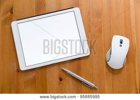 Digital Tablet, pen and mouse on working desk showing a blank screen for advertising