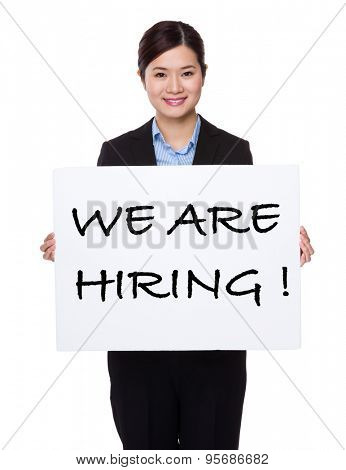 Businesswoman with white palcard for showing phrase of we are hiring