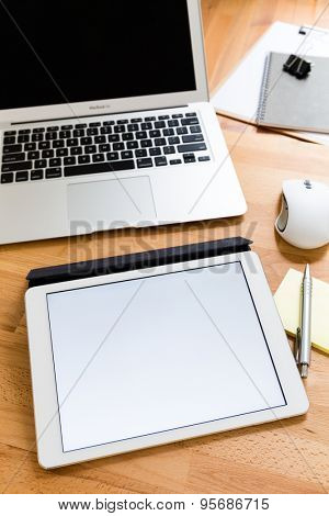 Busy working desk with blank screen of tablet for advertising