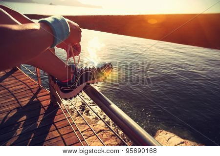 young fitness woman tying shoelace on seaside wooden boardwalk
