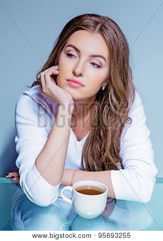 beautiful woman with a cup of coffee against blue background
