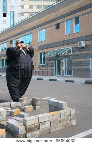 boy in black suit inflatable building brick wall in parking area near house