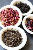 stock photo of rose bud  - Rose bud tea in the vintage spoons on the black stone desk - JPG