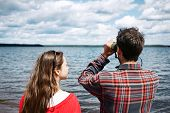 picture of binoculars  - close up portrait back of men and women looks through binoculars while fishing on vacation with lake in background - JPG