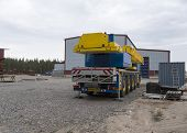foto of boom-truck  - Industrial crane parked in front of a building and a container - JPG