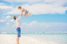 foto of barefoot  - Young happy father playing with his little son standing barefoot at the beach with ocean and beautiful clouds on background - JPG