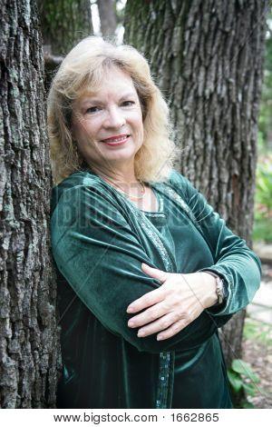 Mature Blond Leans On Tree