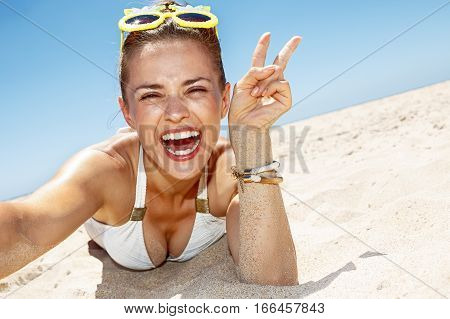 poster of Woman Taking Selfies And Showing Victory Gesture At Sandy Beach