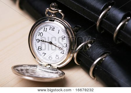 pocket watch with black notebook