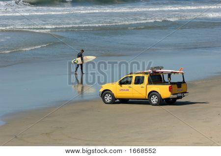 Surfer Walks Beach