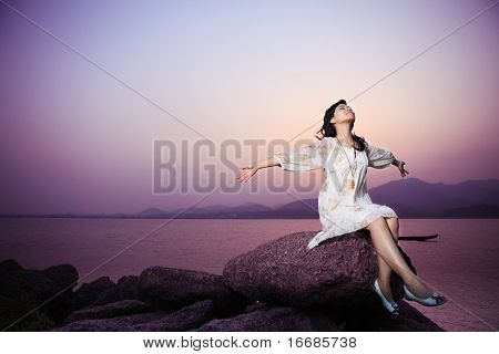 young asian women relax on rock