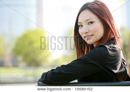 yong asian women sitting on chair outside