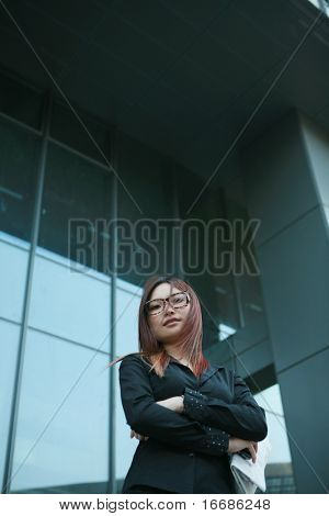 young businesswoman holding newspaper and mobile phone standing before offcie building