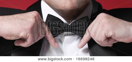 man's hands holding tie
