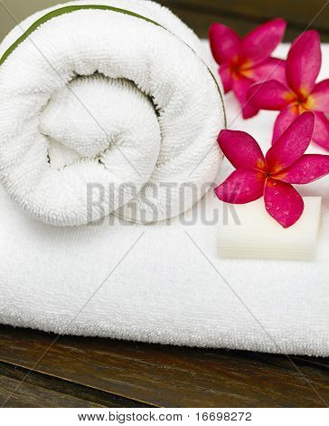 spa objecs with flowers towels on wooden table
