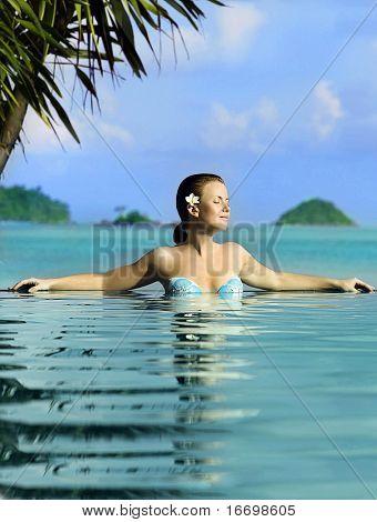 beautiful woman swimming in the pool near the ocean