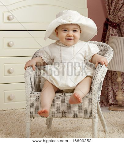 baby girl at home sitting in armchair smiling at children's room