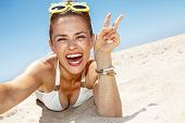 Woman Taking Selfies And Showing Victory Gesture At Sandy Beach poster