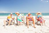 Senior friends reading books on beach chairs at the beach poster