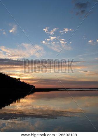 Beautiful sunset over Belorussian lake Naroch split by foreland line