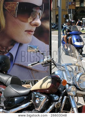 Chopper against a billboard with a young woman in sunglasses