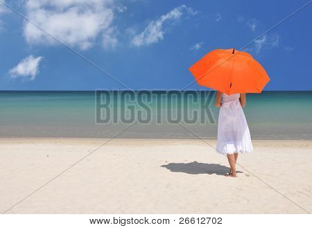 Girl with an orange umbrella on the sandy beach